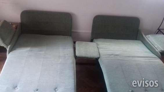 Dos camas individuales separadas con una mesa de luz